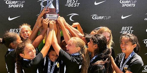 huddle of girls with trophy beach fc club soccer girls surf cup champions 2018